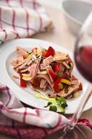 piatto di insalata tedesca di wurst accanto a bicchiere di vino rosso. foto