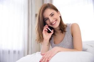 donna sorridente che parla al telefono foto
