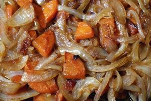 cipolle fritte e carote in padella, uno sfondo luminoso foto