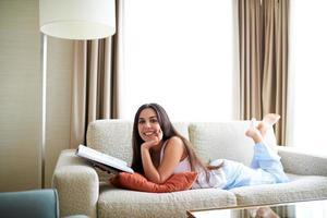 donna sdraiata sul divano con il mento appoggiato in mano. foto