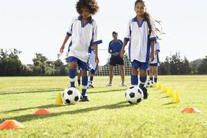 gruppo di bambini nella squadra di calcio che si allena con l'allenatore foto