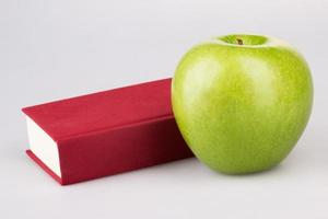 mela verde con libro rosso su sfondo bianco foto