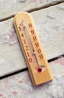 termometro di legno della stanza sulle schede con cemento foto