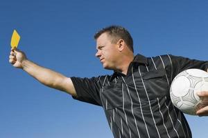 arbitro di calcio che tiene cartellino giallo foto