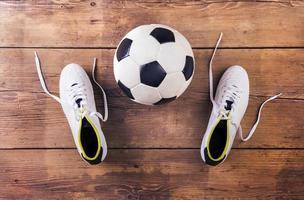 scarpe da calcio e calcio su un pavimento di legno