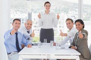 squadra di affari che sorride alla macchina fotografica che mostra i pollici in su