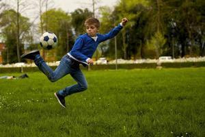 il bambino gioca a calcio foto