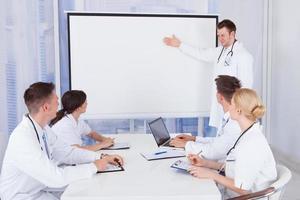 medico maschio che dà presentazione ai colleghi in ospedale foto
