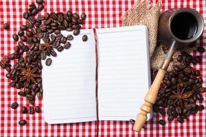 carta bianca, chicco di caffè e tazza di caffè su legno foto