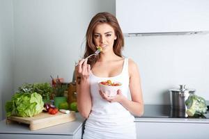 la donna sta mangiando un salat in una ciotola foto