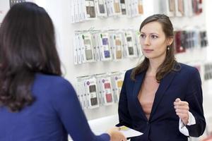 donna che lavora in un negozio con i telefoni foto