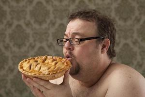 maschio senza camicia, sovrappeso tiene la torta fino alla bocca