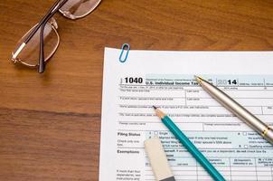 compilando il modulo di dichiarazione dei redditi individuale 1040 nella tabella foto