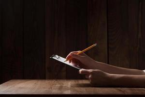 primo piano della mano della donna, scrivendo su carta sul tavolo di legno foto