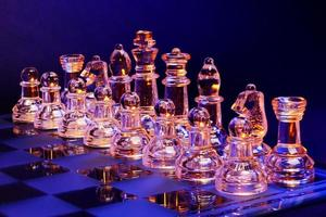 scacchi di vetro sulla scacchiera illuminata dalla luce blu e arancione