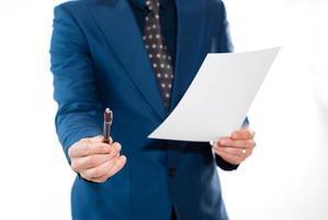 uomo d'affari che tiene una penna e un contratto foto