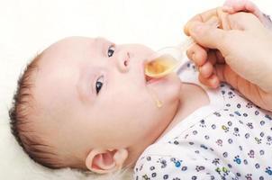 bambino di 3,5 mesi che beve il succo foto