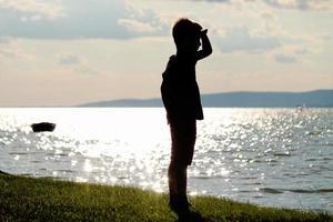il ragazzo distoglie lo sguardo sulla spiaggia foto