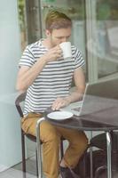 studente sorridente che beve bevanda calda foto