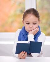 la bambina sta leggendo un libro foto