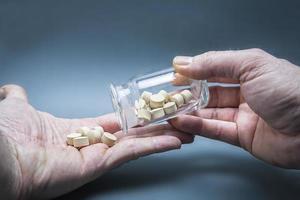 pillole mediche in una mano versata da una bottiglia trasparente foto