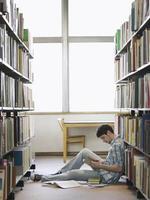 studente universitario leggendo in biblioteca foto