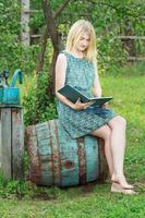 ragazza studentessa a piedi nudi nel libro di lettura del giardino con copertina blu foto