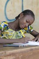 educazione per i bambini africani: scrivere lettere con matite colorate foto