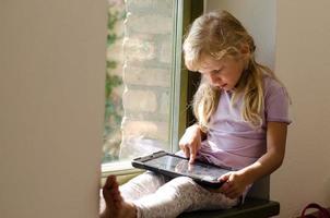 bambina con dispositivo da tavolo foto