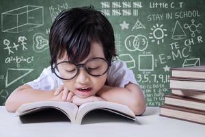 lo studente della scuola elementare legge i libri di testo in classe foto