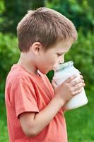 il ragazzo beve latte fresco foto