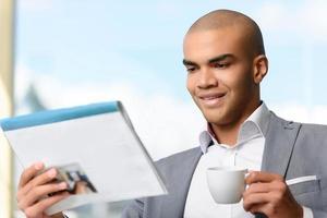 uomo d'affari piacevole che beve caffè foto