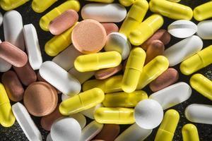 pila di diverse pillole colorate foto