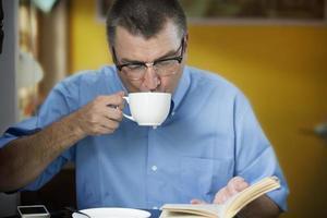 uomo che beve e legge foto