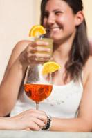giovane donna felice che beve foto