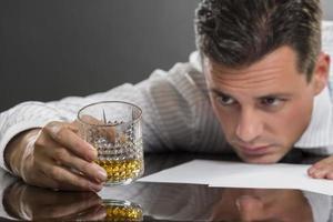 uomo d'affari triste che beve alcool foto