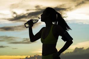 il corridore beve acqua dopo l'allenamento foto