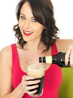 attraente giovane donna che beve birra foto