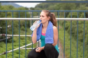 giovane donna che beve acqua in bottiglia foto