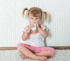 la ragazza felice beve il latte foto