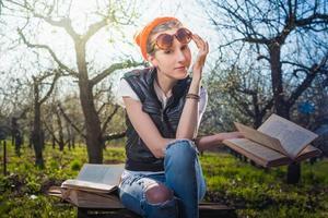 donna nel parco all'aperto con tablet e libro decidere cosa