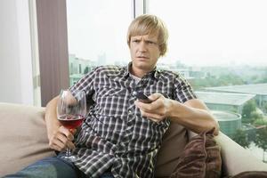 uomo con un bicchiere di vino a guardare la televisione sul divano di casa