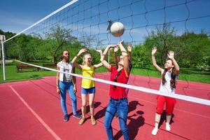 gli adolescenti giocano durante la partita di pallavolo nel parco giochi foto