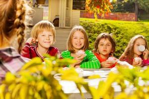 i bambini felici si siedono al tavolo di legno a bere il tè