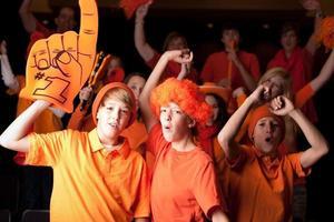 appassionati di sport: adolescenti bambini entusiasti spettatori squadra colore arancione