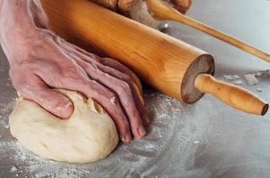 mani di uomo che producono pasta lievitata per pasticceria estone foto