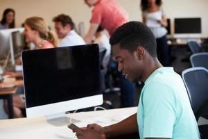 studente di college maschio che utilizza telefono cellulare nell'aula foto
