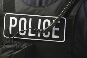 cartello e cavo di poliziotto su giacca protettiva foto