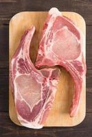 braciole o cotolette di maiale fresche su fondo di legno. foto