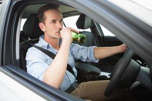 uomo che beve birra durante la guida